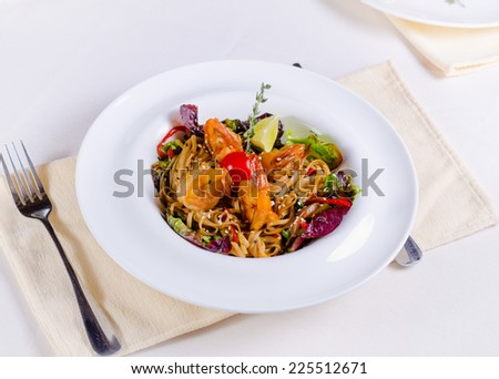 Speciality pasta recipe with grilled shrimps or prawns, fresh herbs and vegetables garnished with lime served at table - stock photo