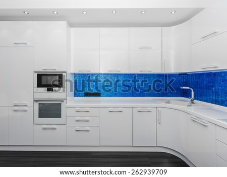 Specious modern white blue interior kitchen-dining room with the built-in household appliances  - stock photo