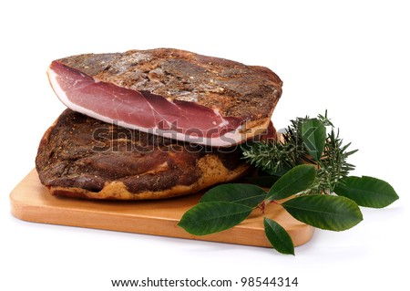 Speck, typical ham Alto Adige, Italy on wooden board