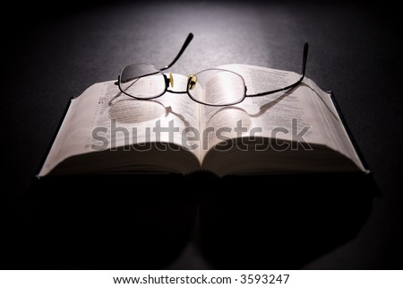 Spectacles and holy bible, shot with dramatic lighting