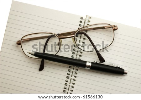 Spectacles and pen lying on notebook