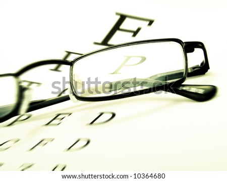 Spectacles on an optometrist chart - stock photo