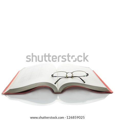 Spectacles on open book - stock photo