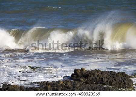 Spectacular  backwash from the  Indian Ocean waves breaking on basalt rocks at  Ocean Beach Bunbury Western Australia on a sunny morning in winter  is foamy white.