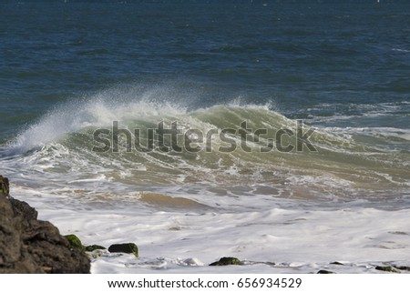 Spectacular backwash from the  Indian Ocean waves breaking on basalt rocks at  Ocean Beach Bunbury Western Australia on a sunny morning in mid winter sends salty spray high into the air.