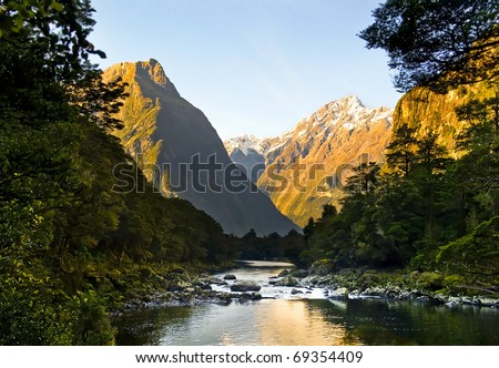 Spectacular mountain peaks and valley with river flowing through it. - stock photo