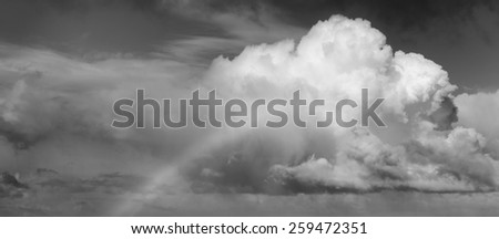 Spectacular rainbow rising up to a huge white cloud with in black and white - stock photo