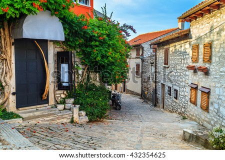Spectacular stone paved street and restaurant entrance with colorful mediterranean flowers, Rovinj old town,Istria region,Croatia,Europe - stock photo