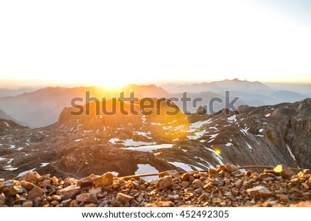 Spectacular sunrise seen from the summit of Hochkoenig mountain (Austria) at 2941m above sea level in the Berchtesgaden alps. Dachstein group in background. Image cross processed.Lens flares from sun. - stock photo