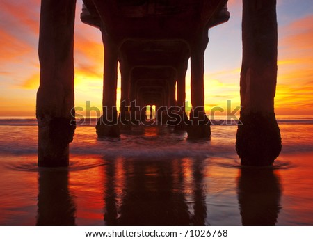 Spectacular sunset coloring beneath a pier in Los Angeles, California. - stock photo