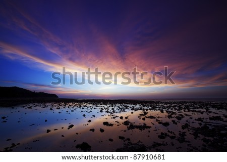 Spectacular sunset over the rocky coast at Nai Yang beach. Phuket island, Thailand. - stock photo