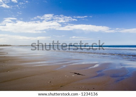 Spectacular view across deserted beach towards Holy Island in Northumbria, England. - stock photo