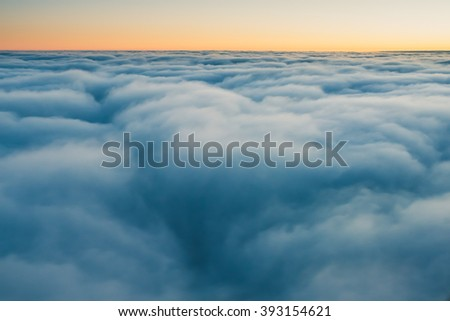 Spectacular view of a sunrise above the clouds from airplane window - stock photo