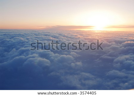 Spectacular view of a sunset above the clouds from airplane window - stock photo
