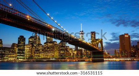 Spectacular view of Manhattan by night from Brooklyn with luminous trail of boats, New York City - stock photo