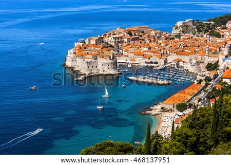 Spectacular view of the city from the sky. Houses, castle, trees, boats and sandals at anchor on the coastline. Colors of the city and sea seem very beautiful in summertime in Dubrovnik, Croatia.