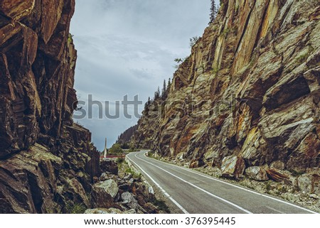 Spectacular view of the famous Transfagarasan road meandering through high rocky steep gorges at an altitude of 2,000 metres in Fagaras mountains, Romania. - stock photo