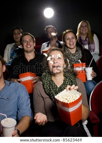 Spectators eating popcorn at the movie theater - stock photo