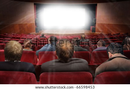 spectators in hall of cinema with movie collage - stock photo