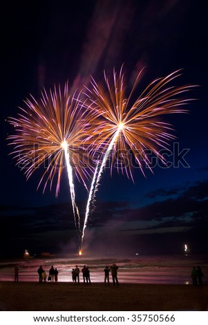 Spectators standing on the beach and looking at fireworks - stock photo