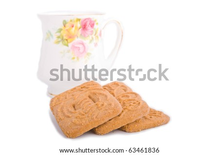 Speculaas dutch cookie stacked in front of bone china tea cup on white - stock photo