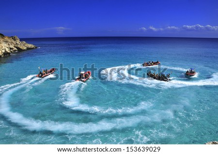Speed boat doing circle on clear blue water - stock photo