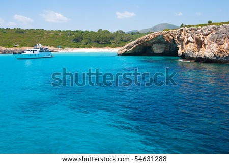Speed boat in a quiet bay with beach and grotto, Majorca island, Spain