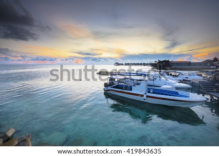Speed boat parking in jetty with dramatic sunset in Mabul Island , Malaysia