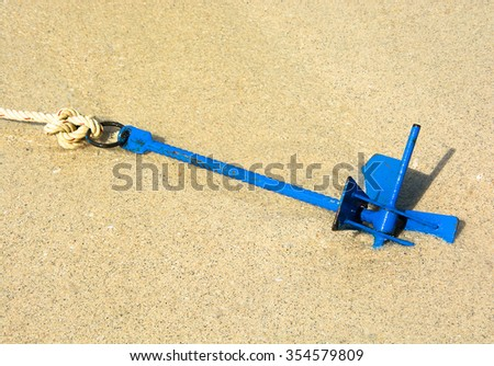SPEED BOAT 'S ANCHOR IN WET BEACH SAND , SANDY BACKGROUND - stock photo