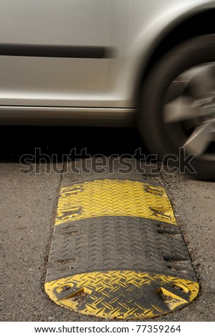 Speed bump on a road when a car is passing - stock photo