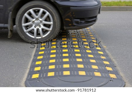Speed bump on a road when and car - stock photo