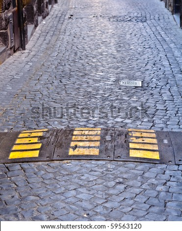 Speed bump on cobbled street - stock photo
