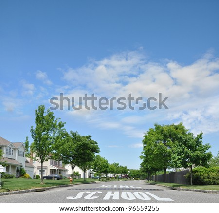 Speed Bump School Crossing Traffic Warning Road Sign on Beautiful Tree Lined Suburban High Ranch style Homes Residential Neighborhood under daytime blue sky with clouds - stock photo
