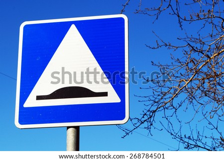 Speed bump sign in blue sky - stock photo