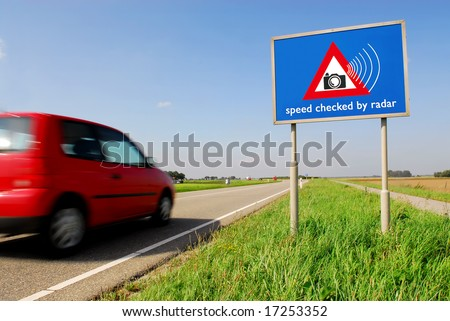 Speed checked by radar roadsign in rural landscape and speeding red car with motion blur - stock photo