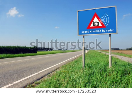 Speed checked by radar roadsign in rural landscape on empty road - stock photo