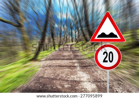 Speed limit and speed bump on Forest road in motion blur on a sunny day - stock photo