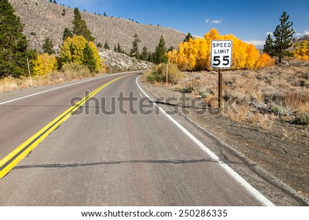 Speed limit by the road with fall colors in the background - no cars. - stock photo