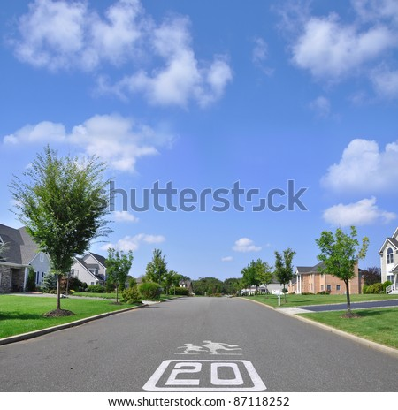 Speed Limit 20 Children Cross symbol on suburban residential neighborhood street under blue sky with clouds - stock photo