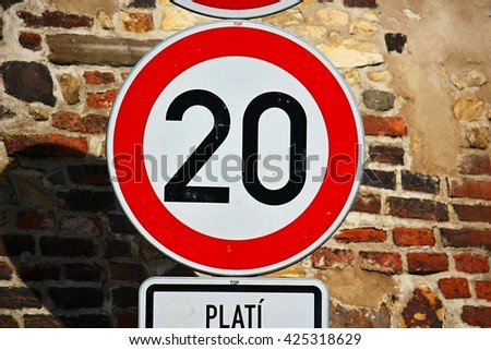 Speed limit 20 km/h traffic sign against brick wall - stock photo