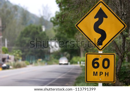 Speed limit sign and winding Road Sign - stock photo