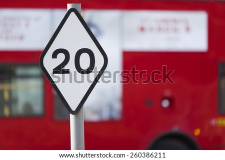Speed limit sign of 20 in a city district with a red blurred bus in the background - stock photo