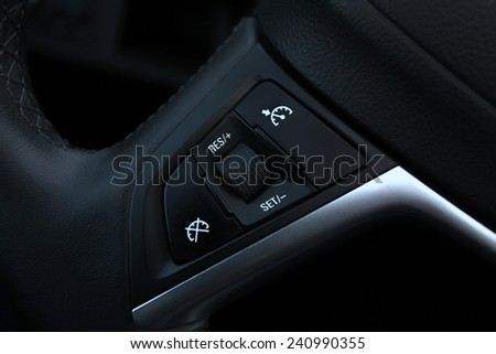 speed limitation and cruise control buttons on a steering wheel in modern car - stock photo