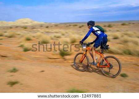 Speed motion mountain biker on desert - stock photo