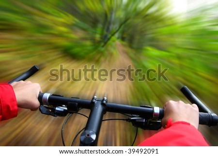Speed on Mountainbike. Biking in the forest motion blurred for speed effect - stock photo