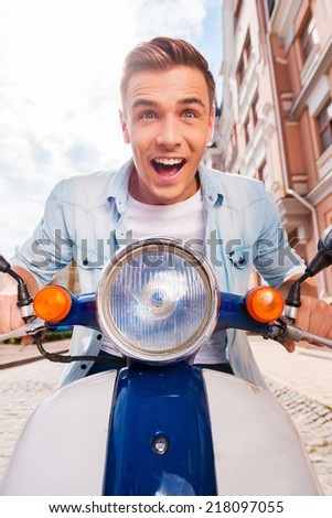 Speed test. Low angle view of happy young man riding scooter along the street and keeping mouth open - stock photo