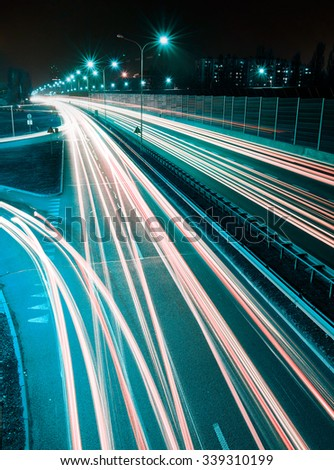 Speed Traffic - long time exposure on highway with car light trails at night - stock photo