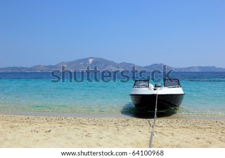 Speedboat anchored on the beach - stock photo