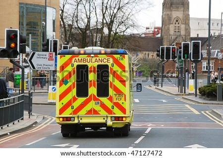 Speeding ambulance in city street responding to emergency call - stock photo