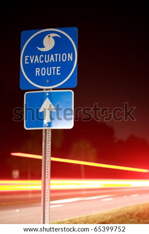 Speeding cars flee an impending storm at night along a hurricane evacuation route. - stock photo